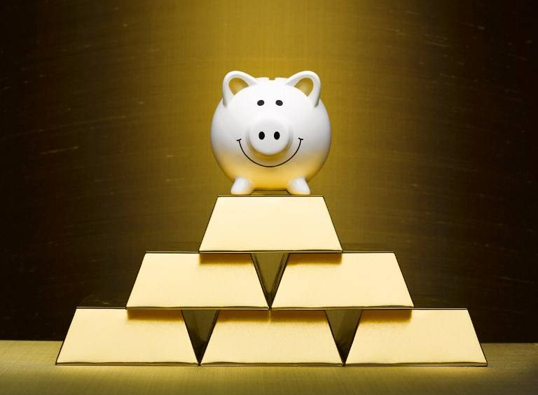 Smiling piggy bank on top of stacked gold bars.