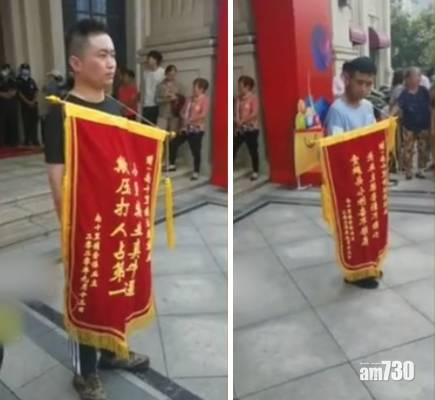 【另類抗議】不滿被迫買車位 鄭州業主贈錦旗諷管理公司